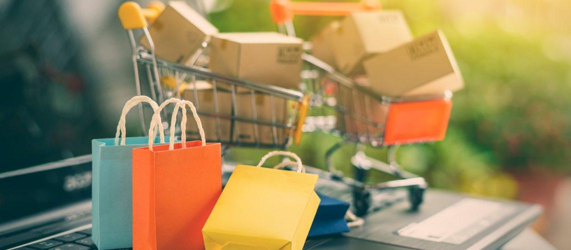E-commerce - Carrinho de supermercado com pacotes de compras feitas pela internet.
